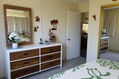 Bedroom with mirrored closet doors and a new dresser